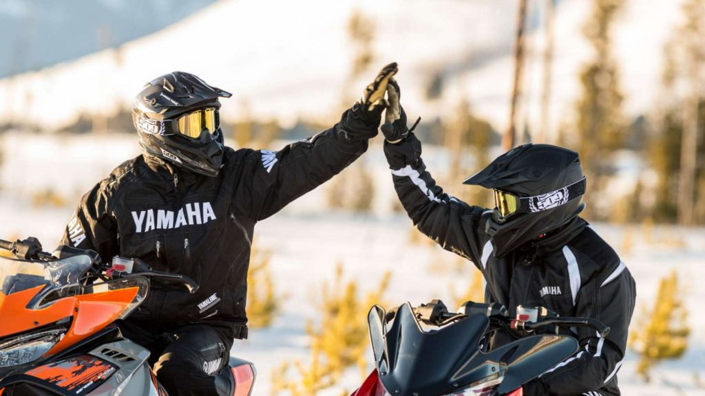 Riders enjoying a high five on their snowmobiles at Horseshoe Valley