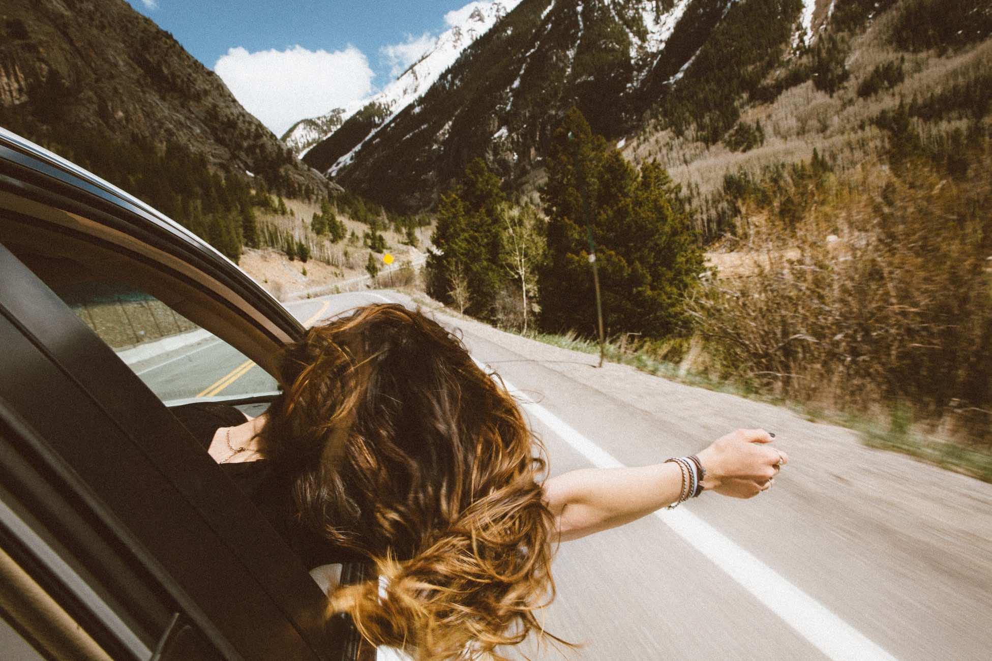Travel with adult children showing woman leaning out of car window