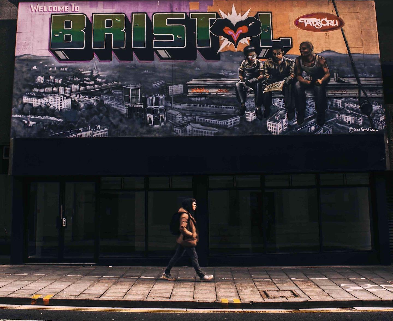 Woman walking past mural fun things to do in Bristol