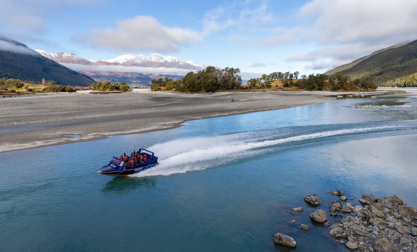 A Dart River Jet Boat zipping along the Dart River at speed with mountains in the background