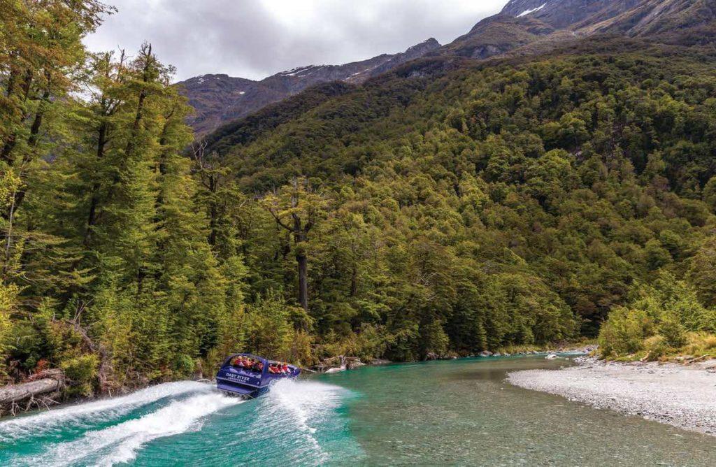 A dart River jet boat speeding along the narrow river