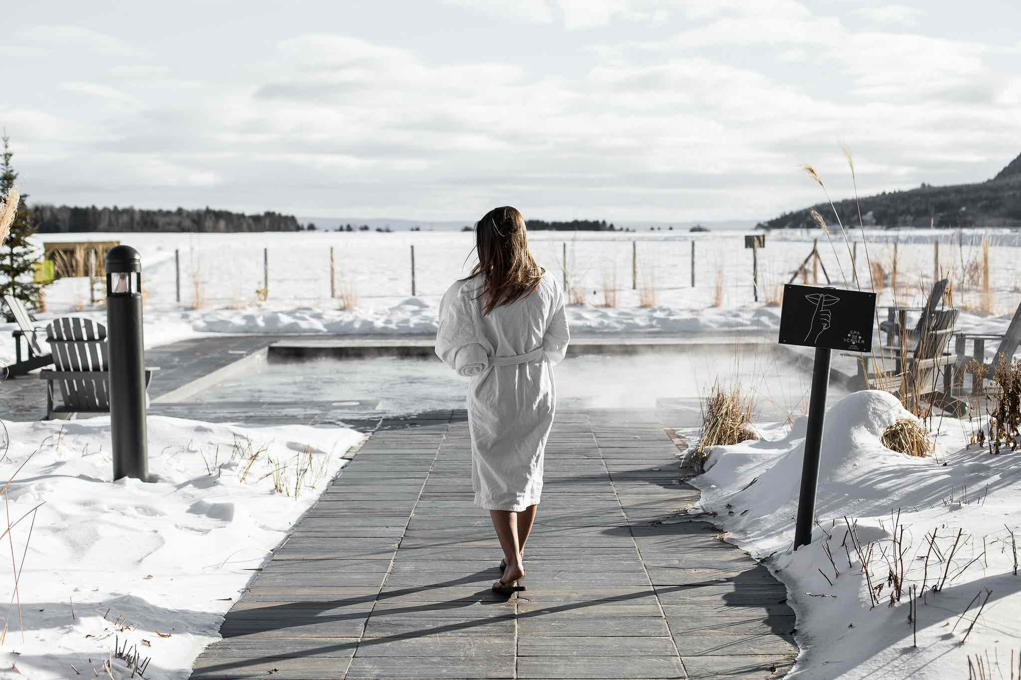 The Bucolic Charm of Quebec's Le Germain Hotel Charlevoix outdoor hot tub in winter with woman in robe