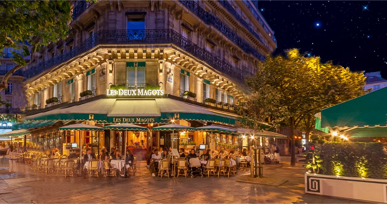 Dining at the Les Deux Magots restaurant at night on the patio like these people is one of the top things to do in Paris for book lovers