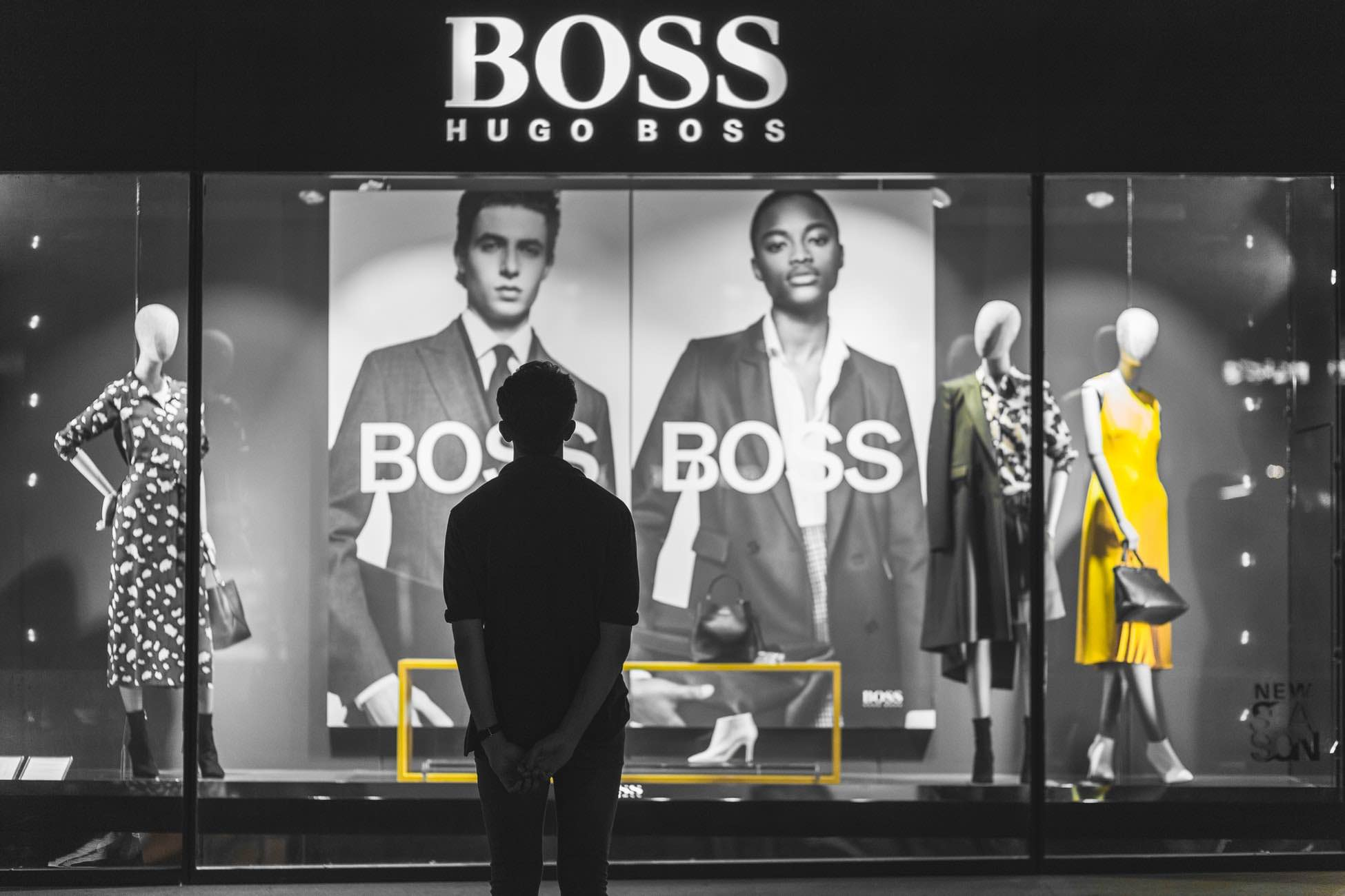 Man window shopping outside Hugo Boss store in Paris-Jules D
