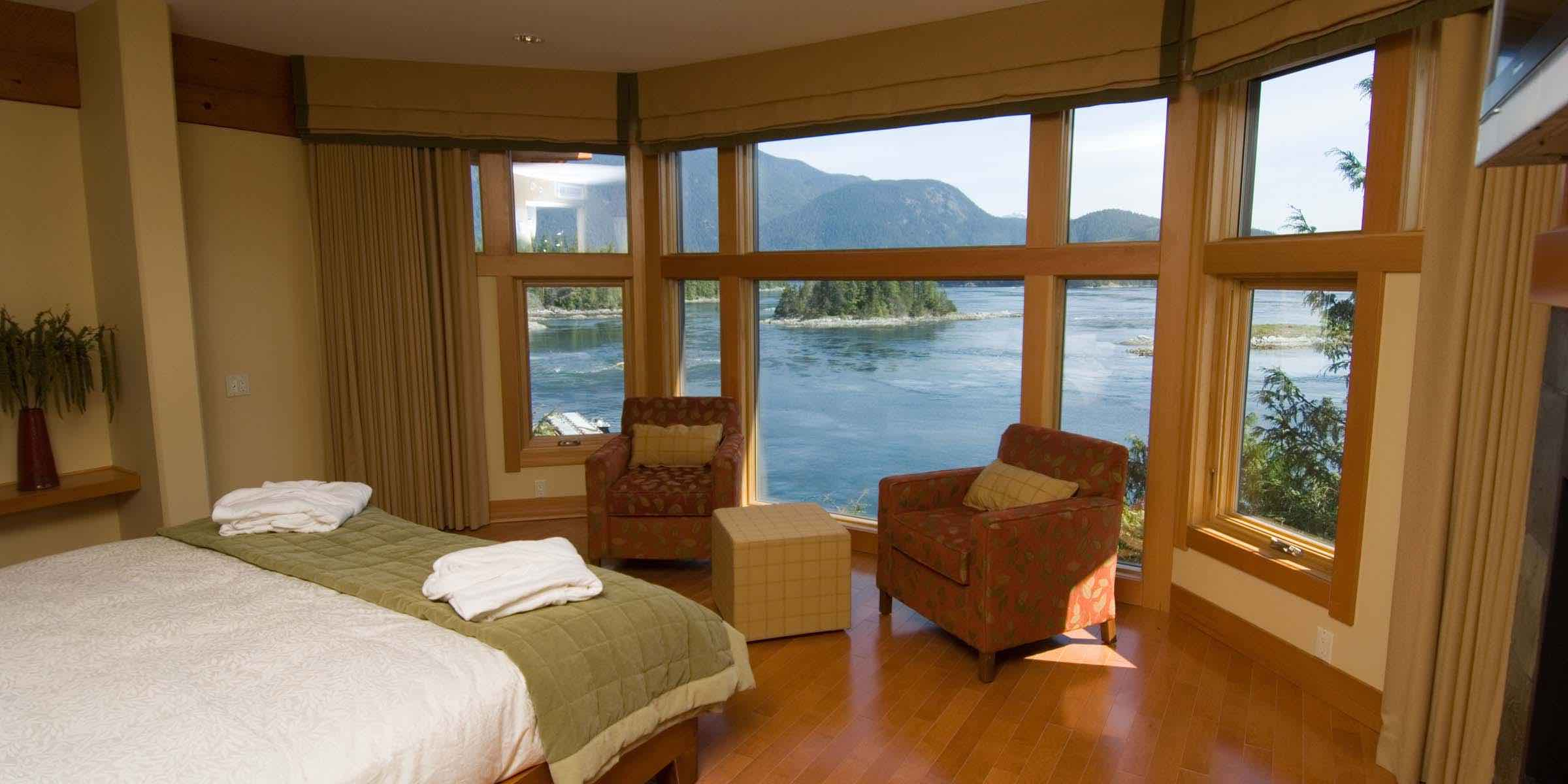 View through the window of a Sonora resort bedroom toward the ocean and mountains
