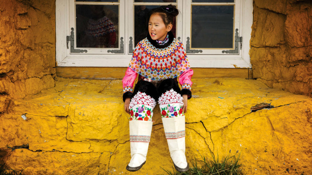 A girl from Greenland in colourful clothing greets tourists aboard Adventure Canada expedition