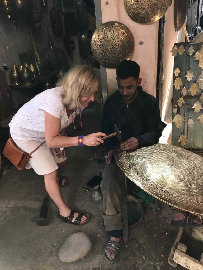 The author tries her hand at  metalworking in the Marrakech Medina souks